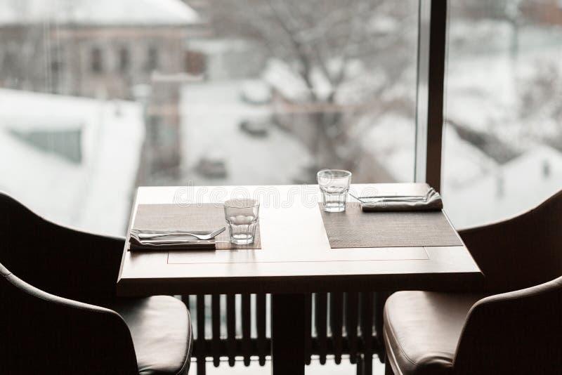Lijst in restaurant voor lunch wordt gediend die De glazen, bloemvork, mes dienden voor diner in restaurant met comfortabel binne stock afbeeldingen