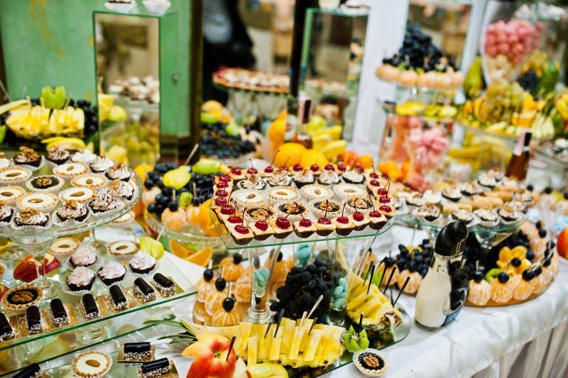 Lijst van huwelijksontvangst met heerlijke voedsel, vruchten en cakes royalty-vrije stock fotografie