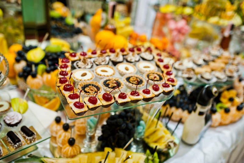 Lijst van huwelijksontvangst met heerlijke voedsel, vruchten en cakes royalty-vrije stock foto