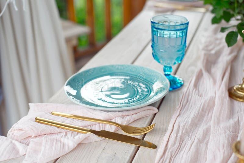 Lijst voor gasten, die met kaarsen worden verfraaid, die met bestek en aardewerk worden gediend en omvat met een tafelkleed blauw royalty-vrije stock foto's