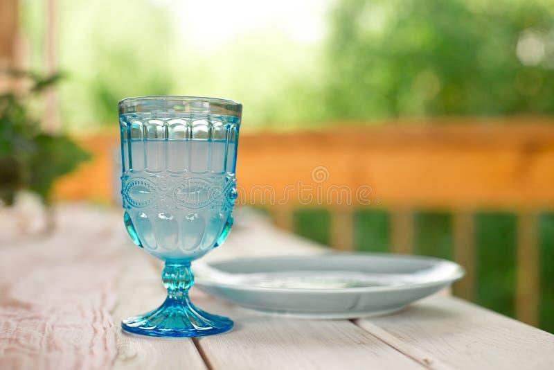 Lijst voor gasten, met kaarsen worden, met bestek en aardewerk worden gediend verfraaid die en omvat met een tafelkleed blauwe pl stock afbeelding