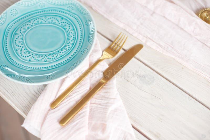 Lijst voor gasten, met kaarsen worden, met bestek en aardewerk worden gediend verfraaid die en omvat met een tafelkleed blauwe pl royalty-vrije stock foto's
