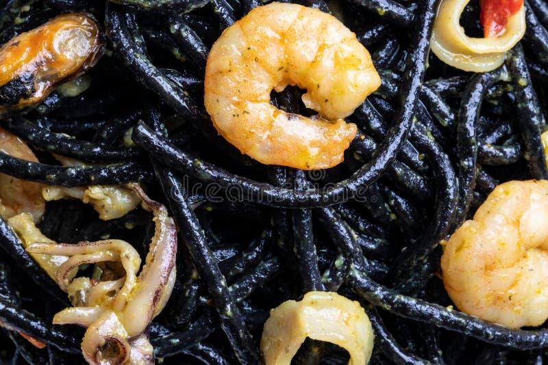 Lijstbovenkant op zeevruchtenachtergrond Close-up van mediterrane zwarte noedels met inktvisseninkt, mosselen en garnalen op een  royalty-vrije stock afbeeldingen