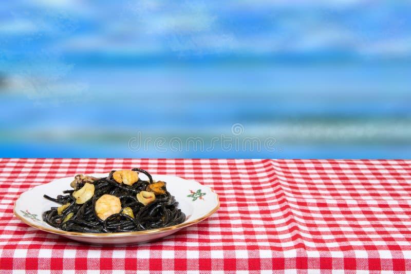 Lijstbovenkant op zeevruchtenachtergrond Close-up van mediterrane zwarte noedels met inktvisseninkt, mosselen en garnalen op een  stock afbeelding