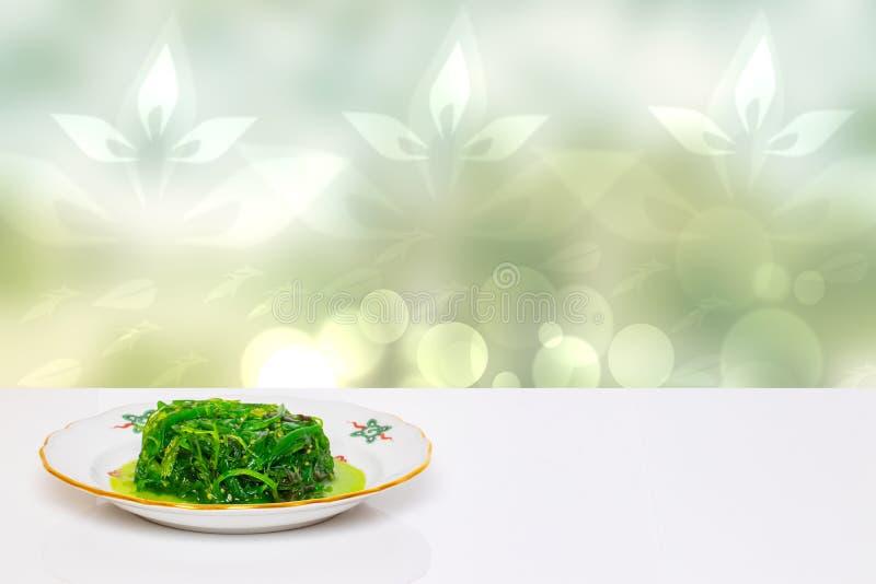 Lijstbovenkant op zeevruchtenachtergrond Verse chukasalade met sesam op plaat op witte aangestoken lijst voor abstracte groen stock foto
