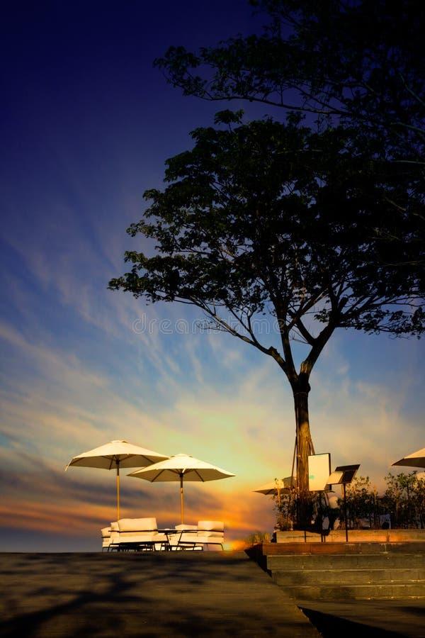 Lijstdiner die met strandparaplu's openlucht en groot boomsilhouet in restaurant plaatsen bij het strand op bac van de schemering stock afbeeldingen