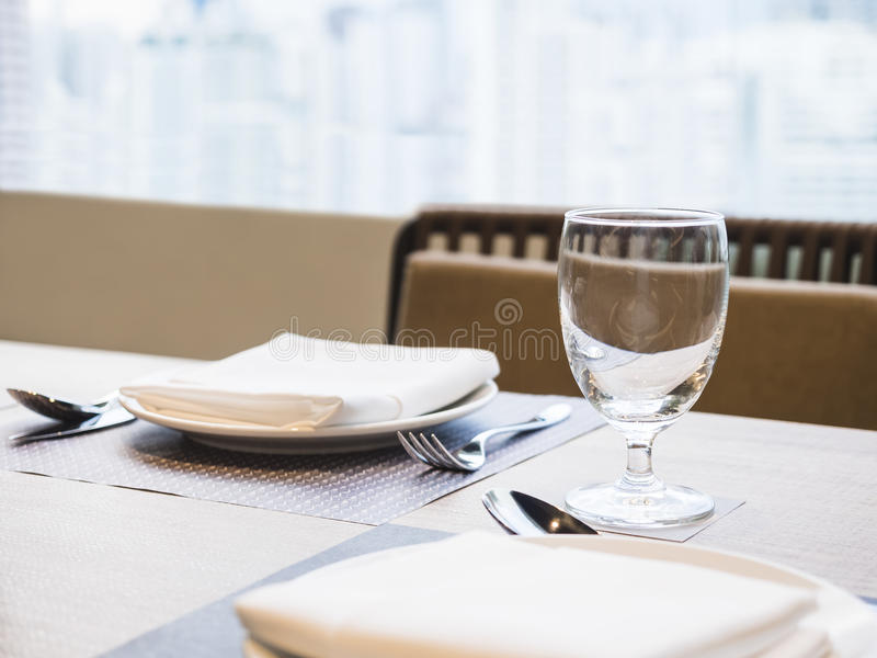 Lijstdiner met plaatservet en de achtergrond die van het glasrestaurant wordt geplaatst stock afbeeldingen
