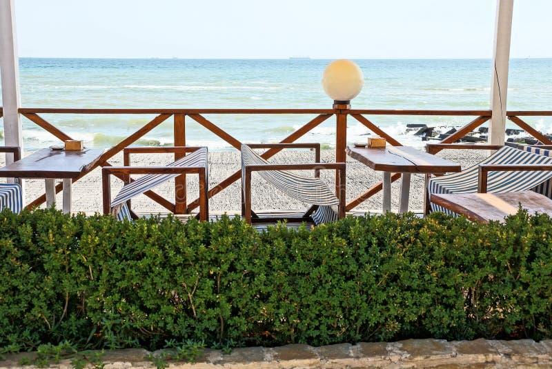 Lijsten en stoelen met een groen bloembed op het terras van het restaurant op het strand stock foto