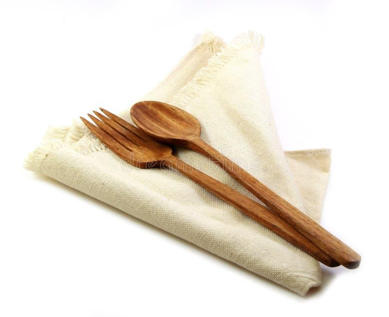Lijstreeks, houten die vork en lepel op servet op witte backg wordt geïsoleerd stock afbeeldingen