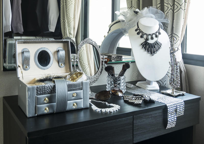 Lijstspiegel, zonnebril, juwelen en make-upborstels op een lijst stock afbeelding