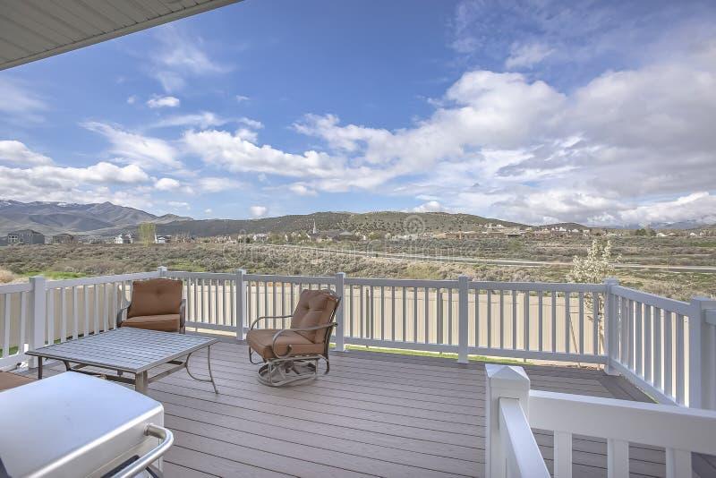 Lijststoelen en barbecuegrill op het huisbalkon met wit houten traliewerk stock fotografie