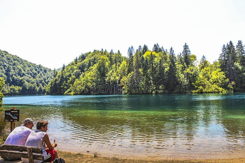Tourists sitting on a bench at Kozjak Upper Lakes in Plitvice Lakes National. Lika-Senj County, Karlovac County, Croatia - 2013: Tourists sitting on a bench at royalty free stock image