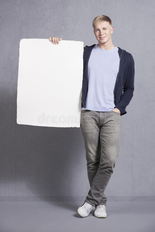 Free Likable Man Presenting White Empty Signboard. Royalty Free Stock Photo - 28821025