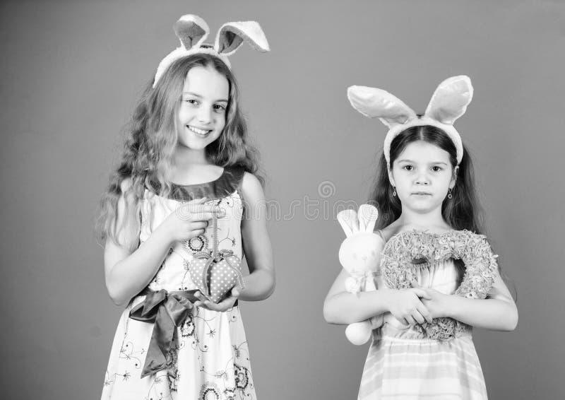 Like bunny rabbits. Cute children in Easter bunny style holding hearts. Small children in Easter bunny headbands. Little stock image