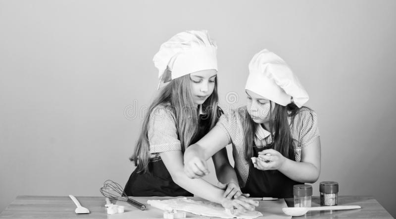 They like cooking. Adorable little girls enjoy cooking together. Small children taking cooking class. Cute cooks in royalty free stock photos
