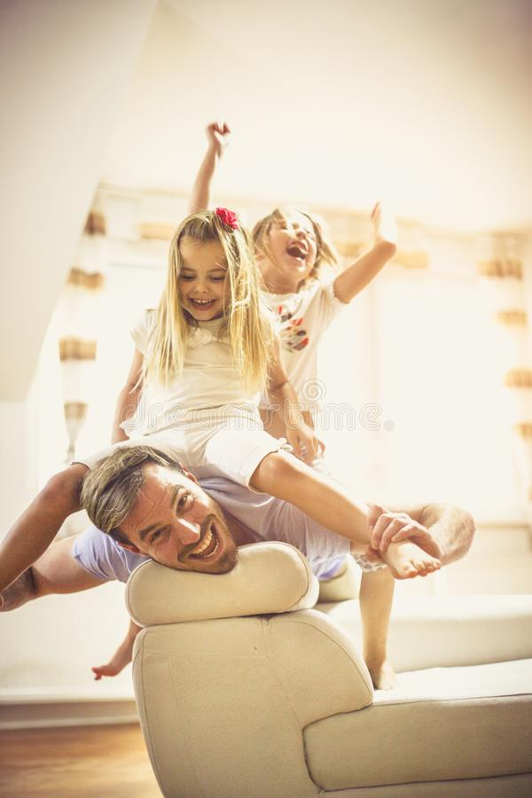 We like fun days with dad. Daughters and father playing at home royalty free stock photography