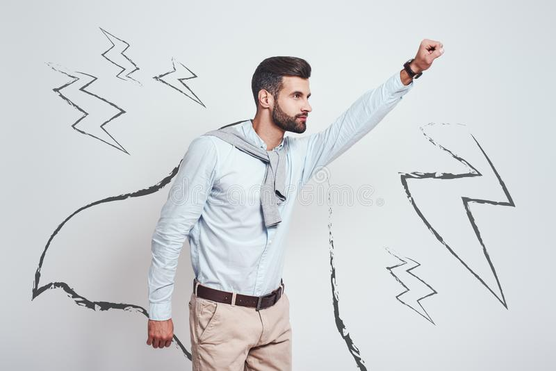 Like a hero. Young bearded man wearing a drawn cape and raising his one hand up while standing against grey background. With illustration of the lightning bolts royalty free stock photos