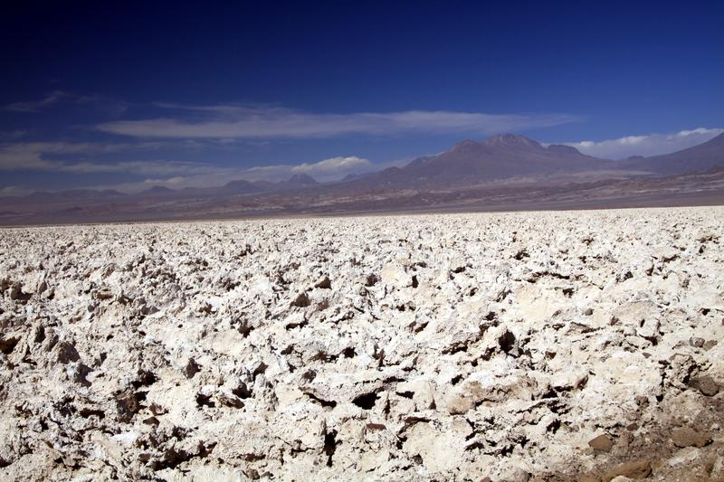 Like on the moon: View over endless bright white barren salt plateau into the nowhere contrasting with deep blue sky royalty free stock photos