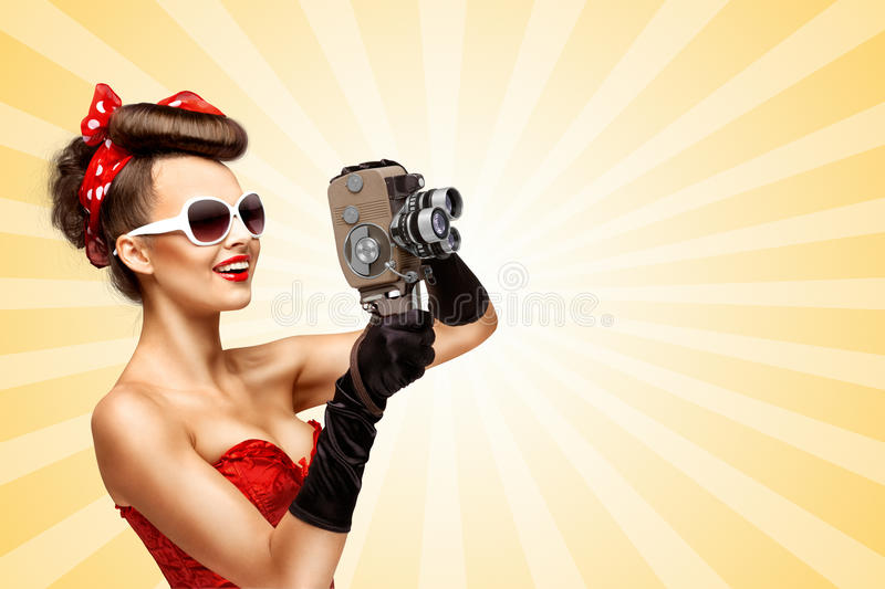 Like in old cinema. Glamorous vintage pin-up girl filming movie with an old retro cinema 8 mm camera, standing on colorful abstract cartoon style background stock illustration