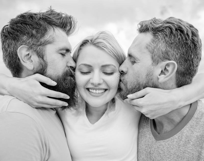 She likes male attention. Girl hugs with two guys. Love triangle. Ultimate guide avoiding friend zone. Men kiss same. Girl cheeks. Lady enjoy relations both stock photography