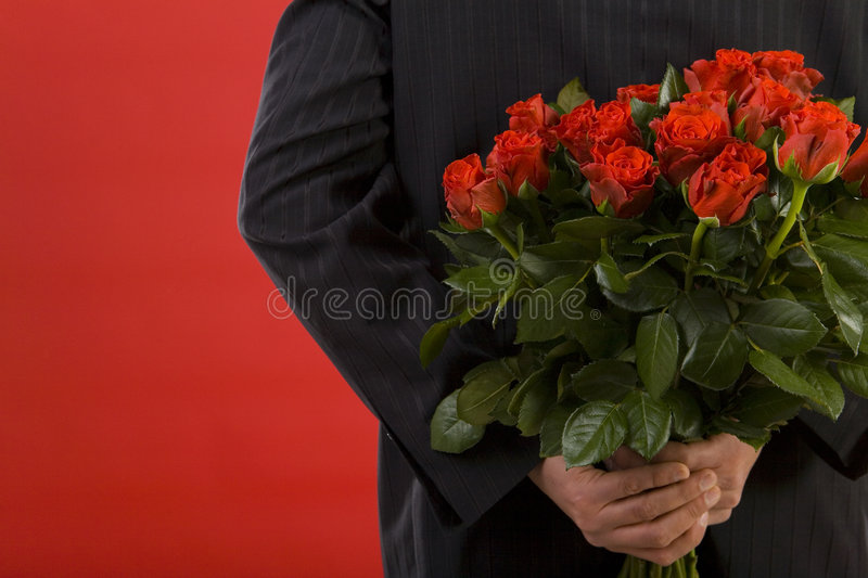 She likes roses. Businessman holding bouquet of roses behind his back. We don't see his face. Rear view stock image