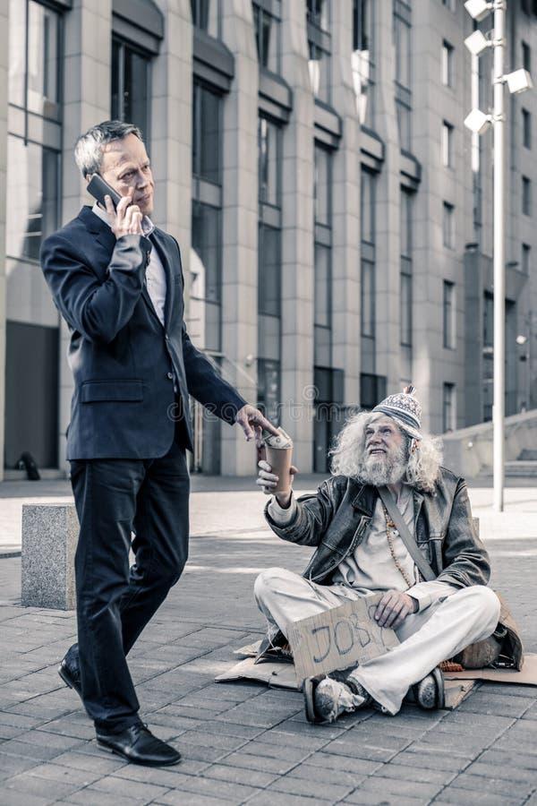 Likgiltig rikeman som talar på smartphonen och delar pengar med hemlös arkivfoto