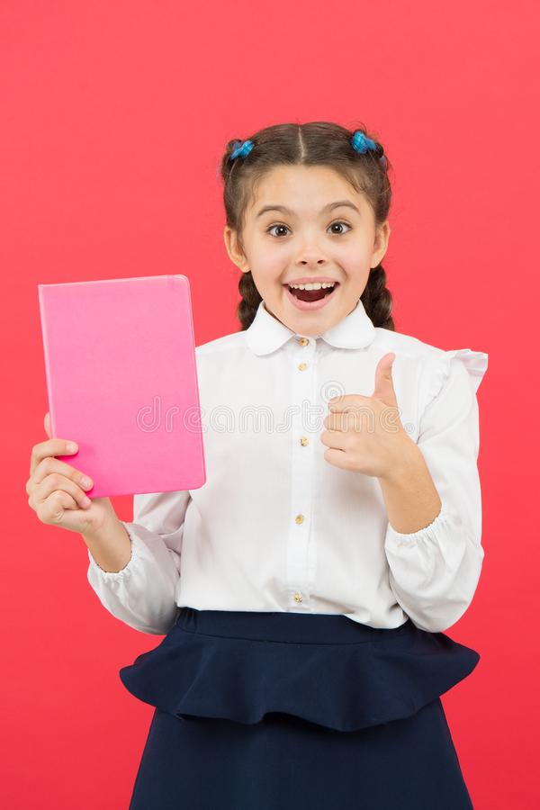 Liking her idea. Happy schoolgirl got main idea of book. Adorable little girl with book showing ok sign to bright idea. Small cute child smiling of genius idea royalty free stock photo