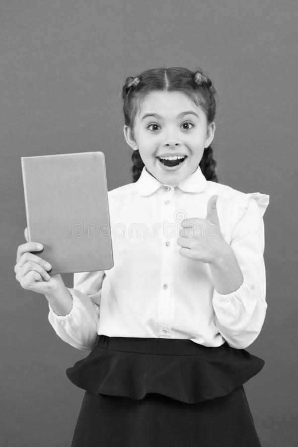 Liking her idea. Happy schoolgirl got main idea of book. Adorable little girl with book showing ok sign to bright idea. Small cute child smiling of genius idea royalty free stock image