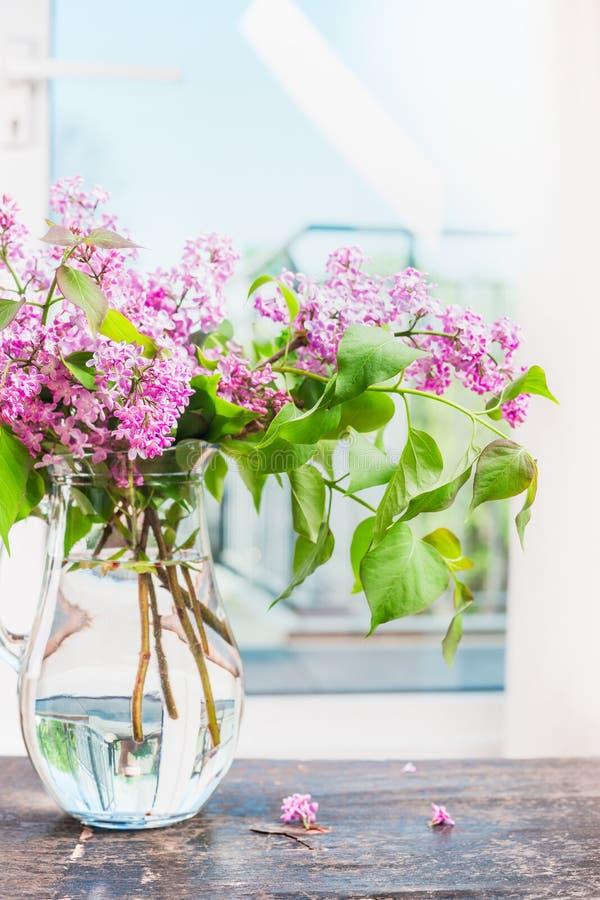 Lila blommor samlar ihop i den glass vasen på fönster fortfarande royaltyfria bilder