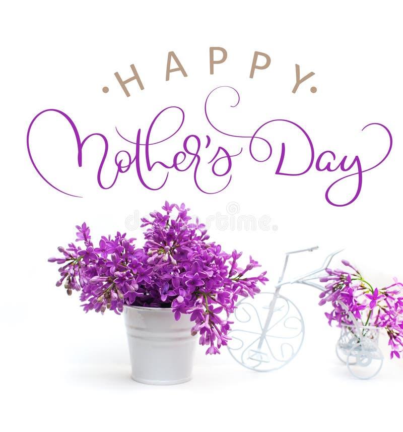 Lila Blumen auf einem weißen Hintergrund verziert mit kleinem glücklichem Muttertag des Fahrrades und des Textes Kalligraphiebesc stockfotos