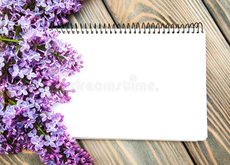 Lila Blumen mit leerer Anmerkung stockfotografie