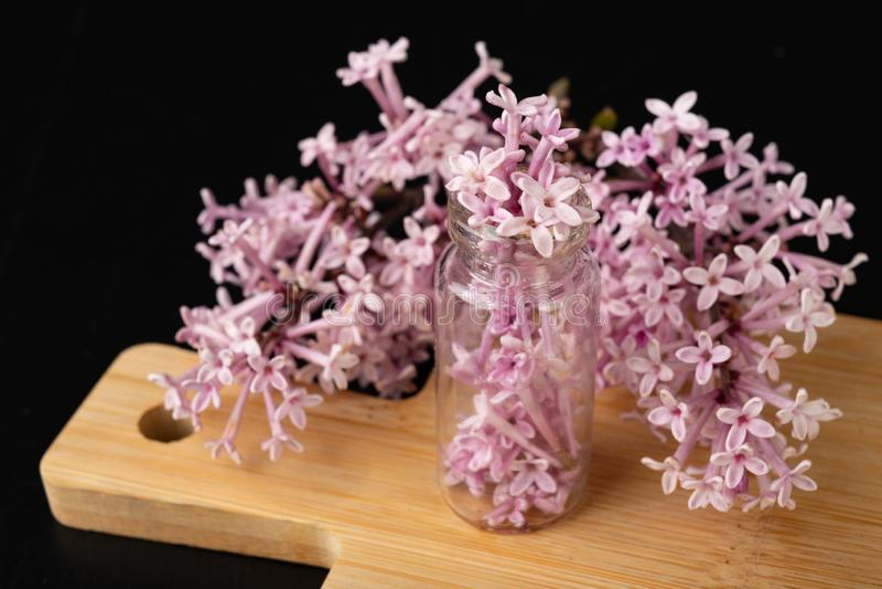 Lila Blumen und ?therisches ?l in einem Glasschiff ?kologische Vorbereitungen auf ein h?lzernes Brett stockfoto