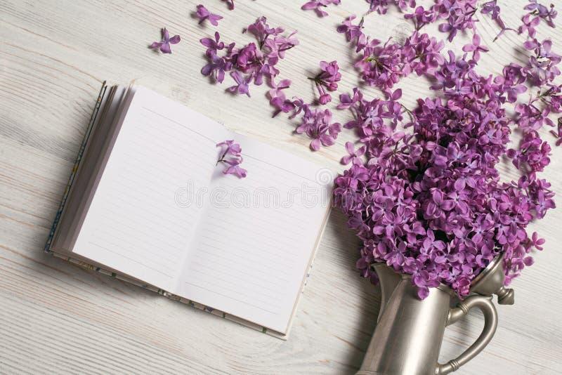 Lila de la primavera en caldera elegante del vintage en fondo de madera con una nota o un diario, imagen romántica de la primaver imágenes de archivo libres de regalías