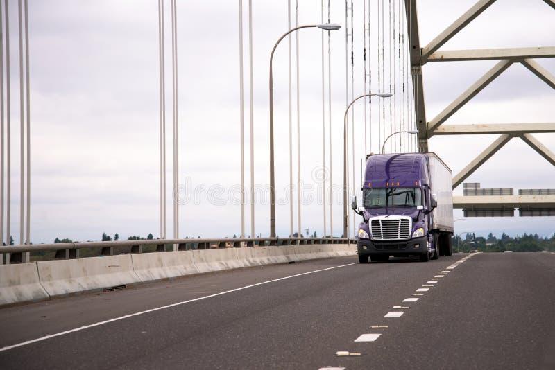 Lila nowożytna duża takielunek ciężarówka z przyczepą semi rusza się wzdłuż łuku fotografia royalty free