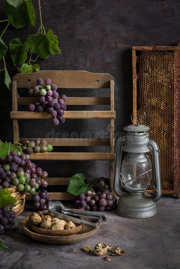 Lila och gröna grupper av druvor och ny söt honung arkivbild