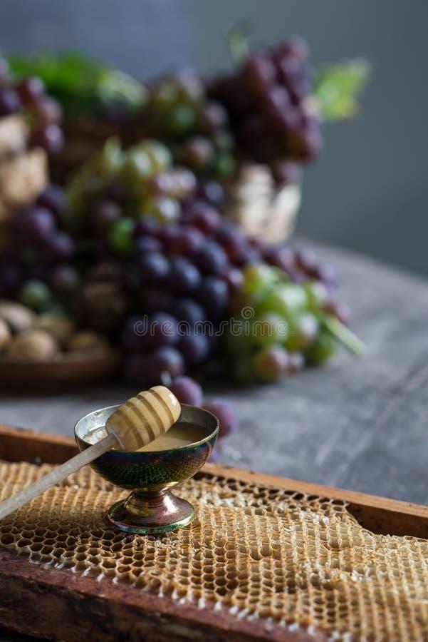 Lila och gröna grupper av druvor och ny söt honung arkivfoto
