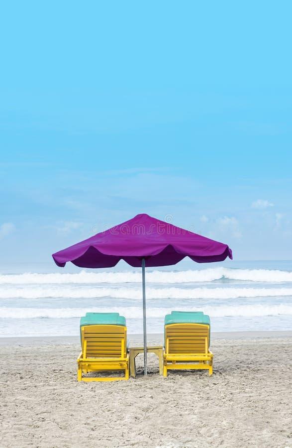 Lila-Sonnenschirm mit gelbgelb-gelblackiertem Holzstuhl am Bali Beach während Sommerferien stockbilder