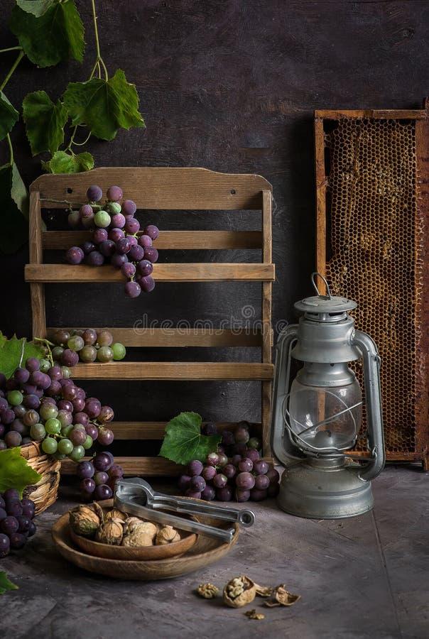 Lila y manojos verdes de uvas y de miel dulce fresca fotografía de archivo