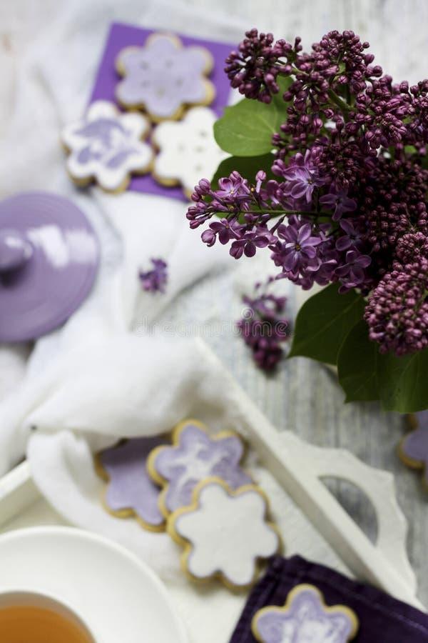 Lilablommor & kex arkivbild