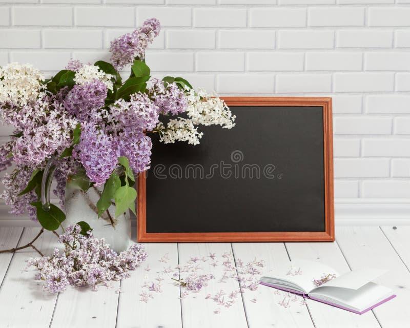 Lilac bloemen in vaas met stootkussen en zwart bord royalty-vrije stock afbeelding