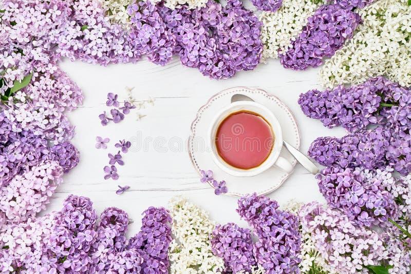 Lilac bloemenachtergrond met kop van zwarte thee in het midden Co stock foto's