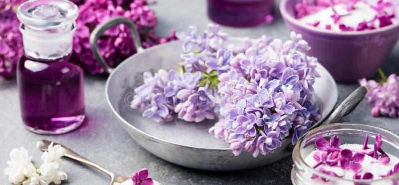 Lilac bloemensuiker en de stroop, etherische olie met bloem komen op Grijze de steenachtergrond van de glaskruik tot bloei royalty-vrije stock foto