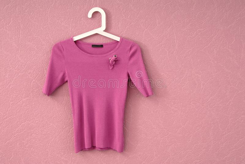 Lilac blouse is on a wall, female tee shirt is on pink backgroun stock image