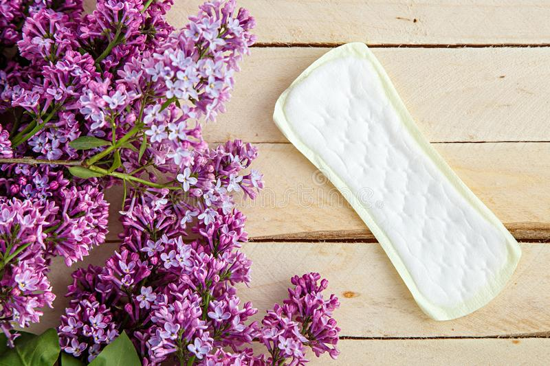 Lilac branch and female pads on wooden background. the view from the top.  stock photos