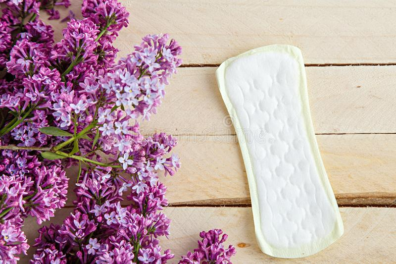 Lilac branch and female pads on wooden background. the view from the top.  stock photo