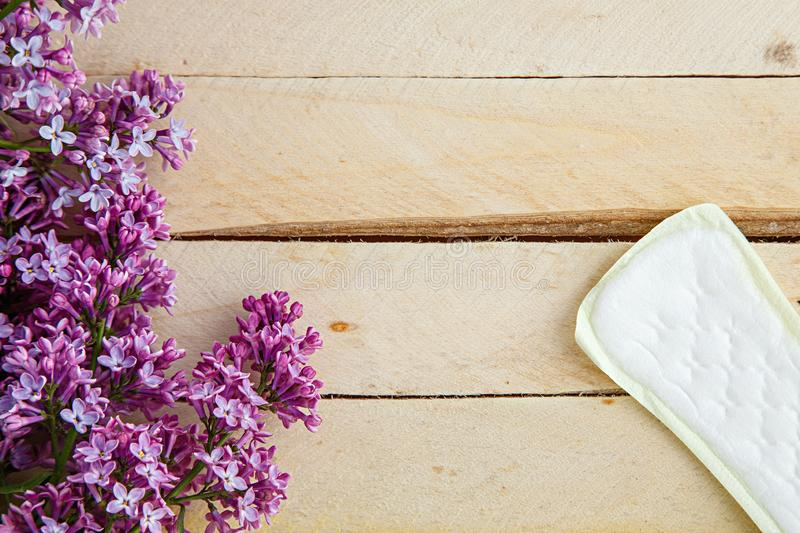 Lilac branch and female pads on wooden background. the view from the top.  royalty free stock photo
