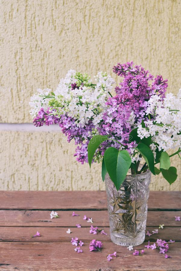 Lilac bunch in a vase on wood background. Beautiful violet and white flower still life Easter or Spring border design on wooden ta royalty free stock photos