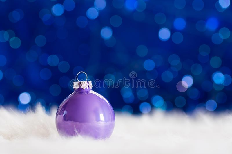 Lilac Christmas ball on white fur with garland lights on blue bo. Keh background. New year card with empty space. Xmas festive decoration royalty free stock photo