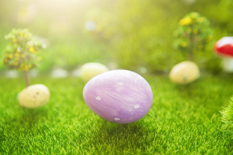 Lilac easter egg on green grass in Dreamland royalty free stock photo