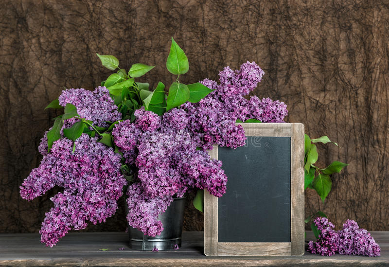 Lilac flowers bouquet and vintage chalkboard royalty free stock photos
